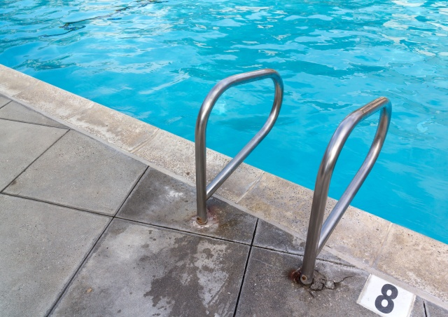 Swimming pool ladder handrail at deep end