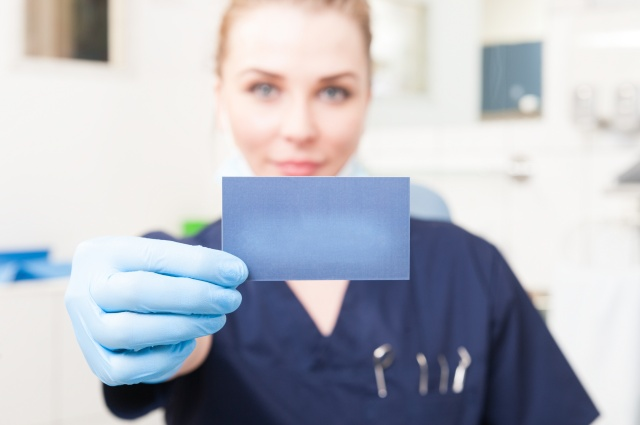 Closeup of business card hold by female dentist with copyspace